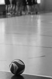 Volleyball in gym. Black and white image of a volleyball lying on gym floor next to the line stock photos