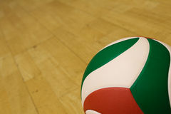 Volleyball in a gym court. Leather volleyball on wooden gym court stock photography