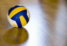 Volleyball on hardwood floor. A professional volleyball lying on a hardwood floor stock image