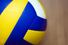 Volleyball on hardwood floor. A professional volleyball lying on a hardwood floor. Very shallow depth of field, focus on the ball, the hardwood floor blurred Royalty Free Stock Images