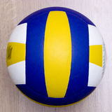 Volleyball on hardwood floor. A professional volleyball lying on a hardwood floor. Very shallow depth of field, focus on the ball, the hardwood floor blurred Stock Photos