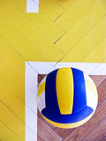 Volleyball on hardwood floor Royalty Free Stock Image