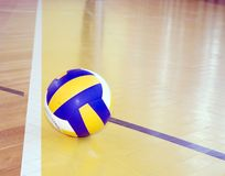Volleyball on hardwood floor. Original official volleyball resting next to the line of a hardwood gym floor royalty free stock photography