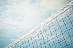 Volleyball Net. A volleyball next against a blue sky with some clouds Stock Photo