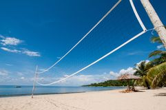 Volleyball net on beach. Volleyball net on idyllic tropical beach with blue sky and cloudscape background royalty free stock image