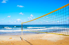 Volleyball net on the beach close-up. Blue cloudy sky and yellow sand on the beach Stock Image