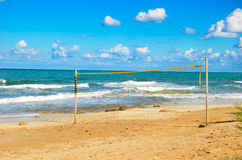 Volleyball net on the beach. Cloudy blue sky and turquoise sea Royalty Free Stock Photos