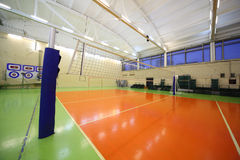 Volleyball net inside lighted school gym hall. With green-orange floor stock images