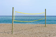 Volleyball net on sandy beach in Spain. Yellow volleyball net on sunny sandy beach in Spain Royalty Free Stock Photography