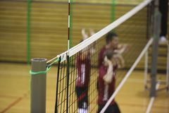 Volleyball net in the sport hall. With players on background Stock Images