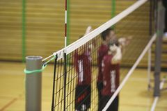Volleyball net in the sport hall. With players on background Royalty Free Stock Image