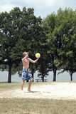 Volleyball Player. A man serving a volleyball on a beach court Stock Photography
