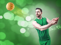 Volleyball player on green uniform on green bokeh background Royalty Free Stock Photography