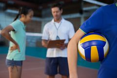 Volleyball player holding ball in court. Mid-section of volleyball player holding ball in court Stock Photos