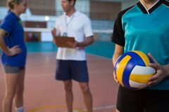 Volleyball player holding ball in court. Mid-section of volleyball player holding ball in court Royalty Free Stock Photos