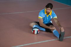 Volleyball player stretching at court. Full length of male volleyball player stretching at court Royalty Free Stock Images