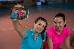 Volleyball player with teammate taking selfie. Female volleyball player with teammate taking selfie at court Stock Image