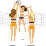 Volleyball Player Woman Smash Attack. Active woman jumping doing smash attack while two athletic volleyball players are blocking ball Stock Photography