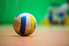 Volleyball separated on wooden floor. Blue yellow and white volleyball on wooden floor Stock Photos