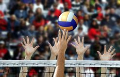 Volleyball spike with hands blocking over the net. Volleyball player spike with hands blocking over the net royalty free stock images