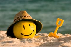 Volleyball With Straw Hat. A yellow smiley faced beach volleyball sits in the summer sand wearing a straw hat Stock Photo