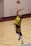Volleyballspieler dient den Ball Stockbild