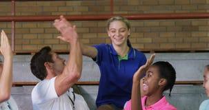 Volleybolllagledare som ger höjdpunkt fem till kvinnliga spelare 4k lager videofilmer
