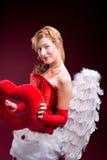 Vollkommener blonder Engel mit einem roten Inneren Lizenzfreie Stockfotografie