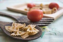 Vollkornteigwaren auf einem hölzernen Schöpflöffel und frischen Tomaten lizenzfreie stockfotos