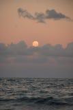 Vollmond über Ozean und Wolken Stockbild