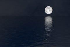Vollmond über Wassernachtszenenhintergrund Stockfoto