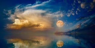 Vollmond, der über ruhigen See im Sonnenunterganghimmel steigt stockfoto