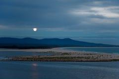 Vollmond, der über See- u. Seelandschaft an der Dämmerung steigt Stockbild