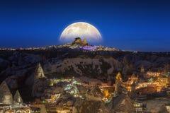 Vollmond, der über Uchisar-Schloss in Cappadocia, die Türkei steigt stockfotografie