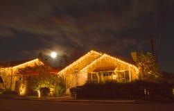 Vollmond ragt über ein Haus mit Weihnachtslichtern empor Lizenzfreie Stockfotos
