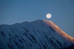 Vollmond während eines Sonnenaufgangs auf dem Hintergrund von Schnee-mit einer Kappe bedeckt in den Himalajabergen in Nepal Stockfotografie