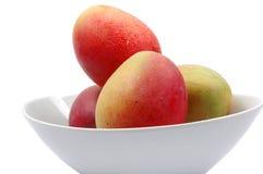 Vollständige Mangofrüchte auf Schüssel Lizenzfreie Stockbilder
