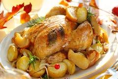 Vollständiges gebratenes Huhn mit Kartoffeln und Äpfeln Lizenzfreies Stockfoto