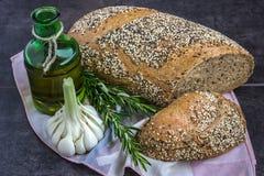 Vollweizenbrot und -roggen, besprüht mit Sonnenblumensamen, Mohn, Samen des indischen Sesams, nahe bei einer Flasche Olivenöl, Ro Lizenzfreie Stockfotografie