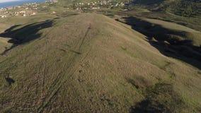 Volo aereo del fuco al tramonto sopra la valle con le colline al giorno soleggiato video d archivio