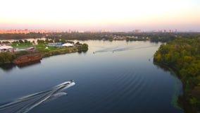 Volo aereo del fuco: La gente guida sul bordo dietro la barca fotografia stock libera da diritti