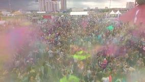 Volo aereo sopra la folla della gente di dancing sul festival di Holi dei colori stock footage