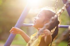 Volo asiatico felice della ragazza del piccolo bambino sull'oscillazione in campo da giuoco immagine stock