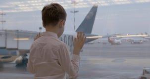 Volo aspettante del bambino ed esaminare gli aerei attraverso la finestra archivi video