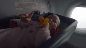 Volo attivo della neonata in aereo in culla speciale stock footage