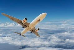 Volo commerciale dell'aeroplano sopra le nuvole ed il chiaro cielo blu più Fotografie Stock