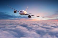 Volo commerciale di jet dell'aeroplano sopra le nuvole drammatiche immagini stock