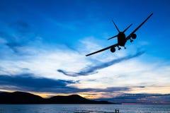 Volo commerciale profilato dell'aeroplano al tramonto Immagini Stock