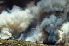 Volo degli aerei con l'aumento bianco denso del fumo dall'incendio violento infuriantesi Immagini Stock