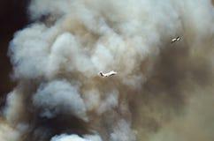 Volo degli aerei con l'aumento bianco denso del fumo dall'incendio violento infuriantesi Fotografia Stock